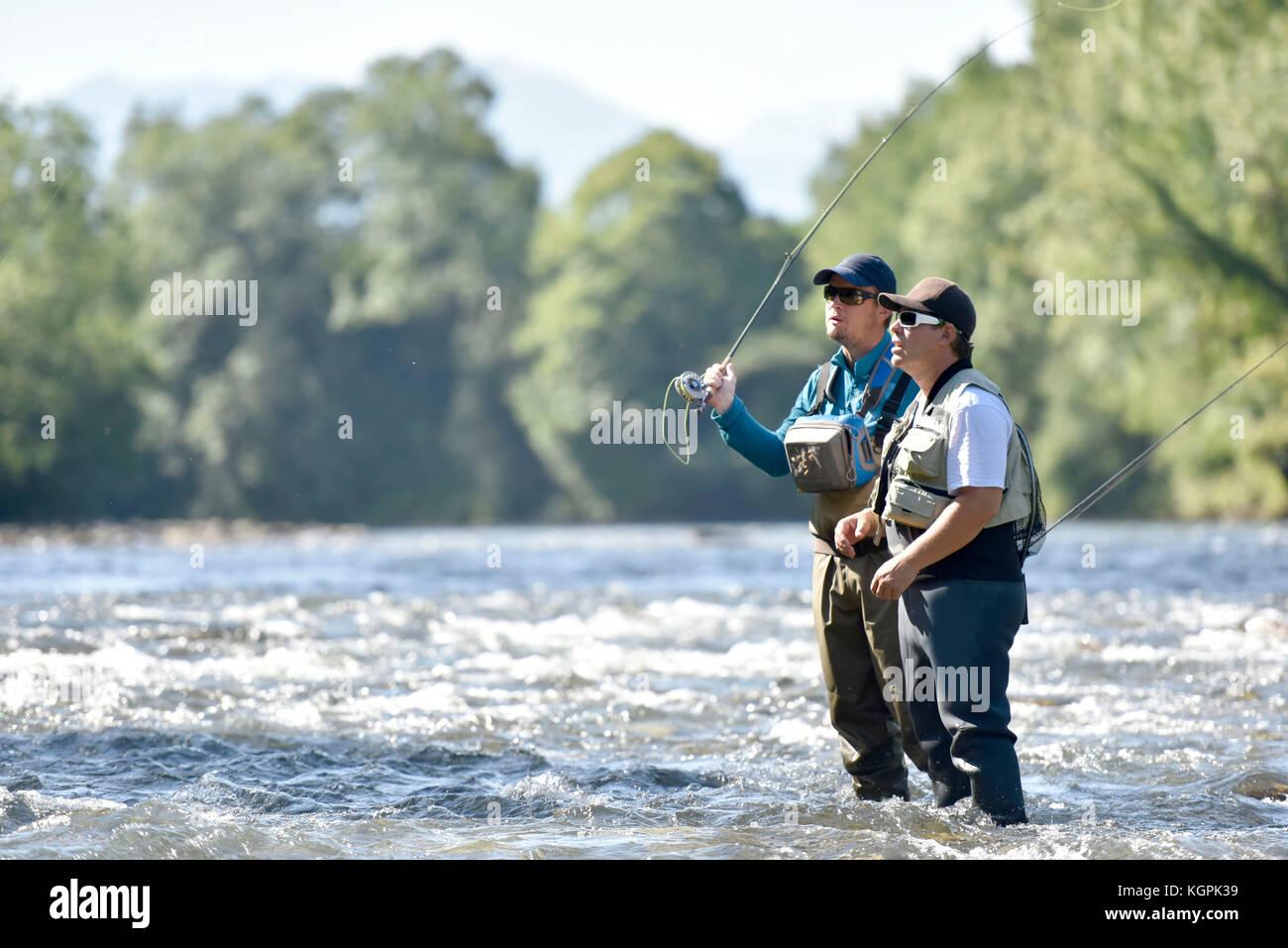 Flyfisherman con guida di pesca in fiume Immagini Stock