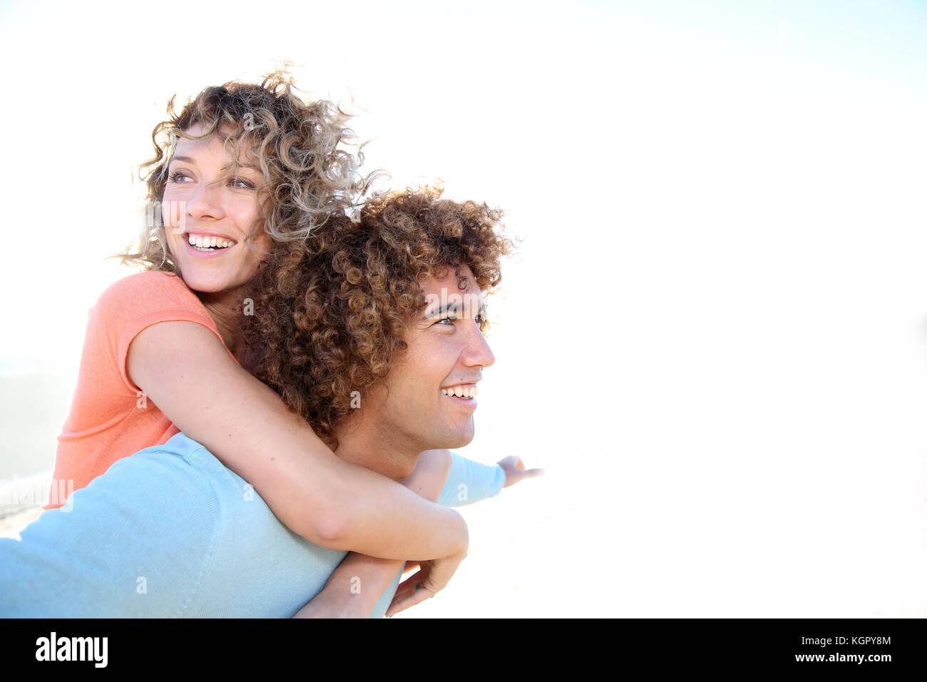 L uomo dando piggyback ride alla ragazza sulla spiaggia Immagini Stock