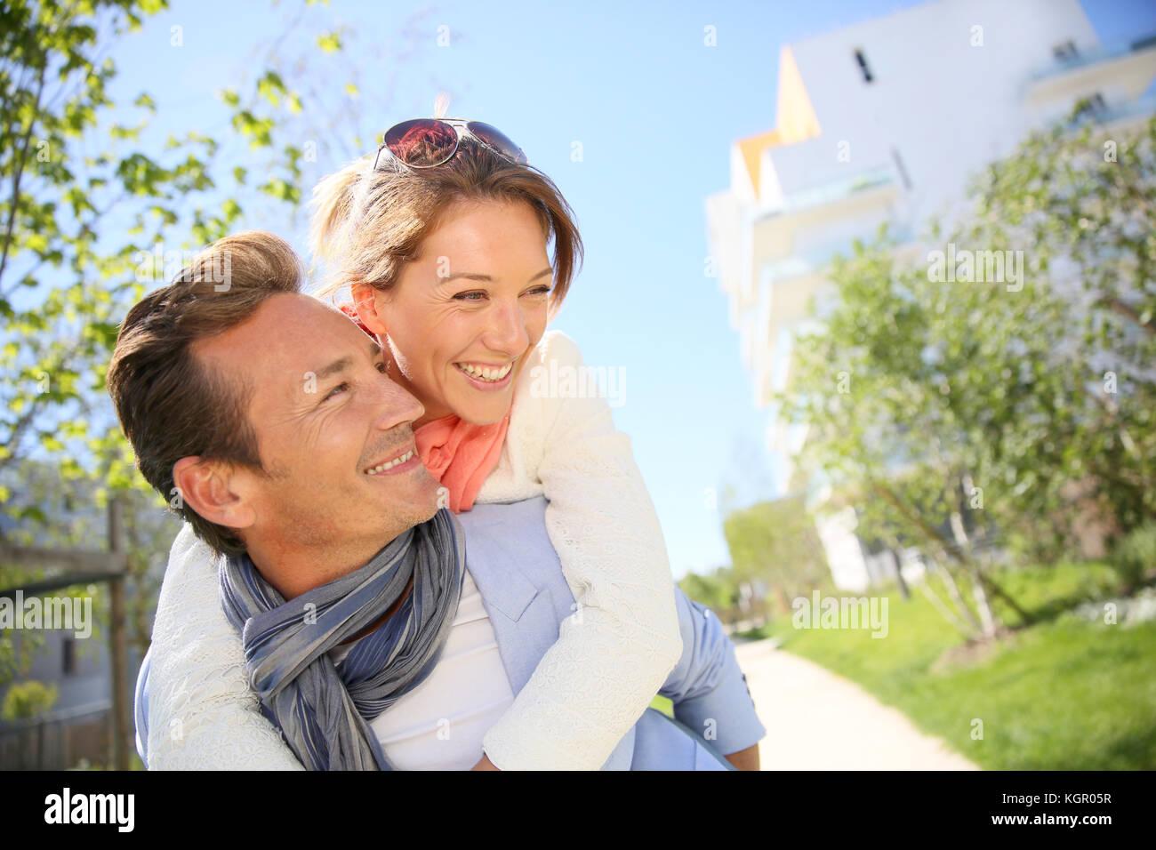 L uomo dando piggyback ride per donna in posizione di parcheggio Foto Stock