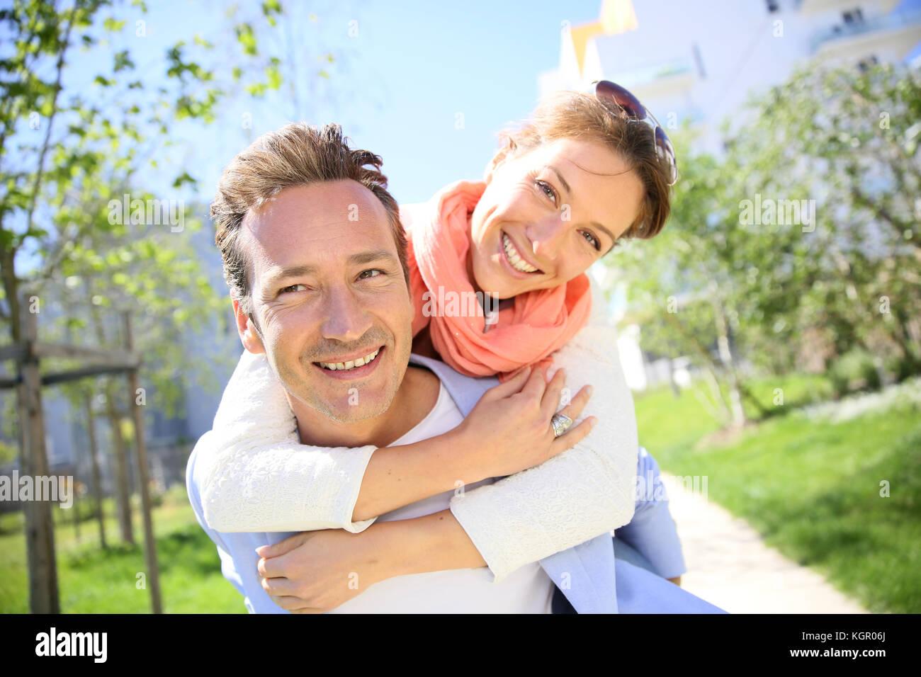 L uomo dando piggyback ride per donna in posizione di parcheggio Immagini Stock