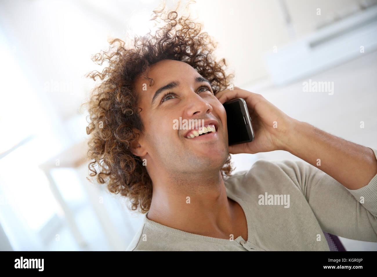 Uomo sorridente in ufficio parlando al telefono cellulare Immagini Stock