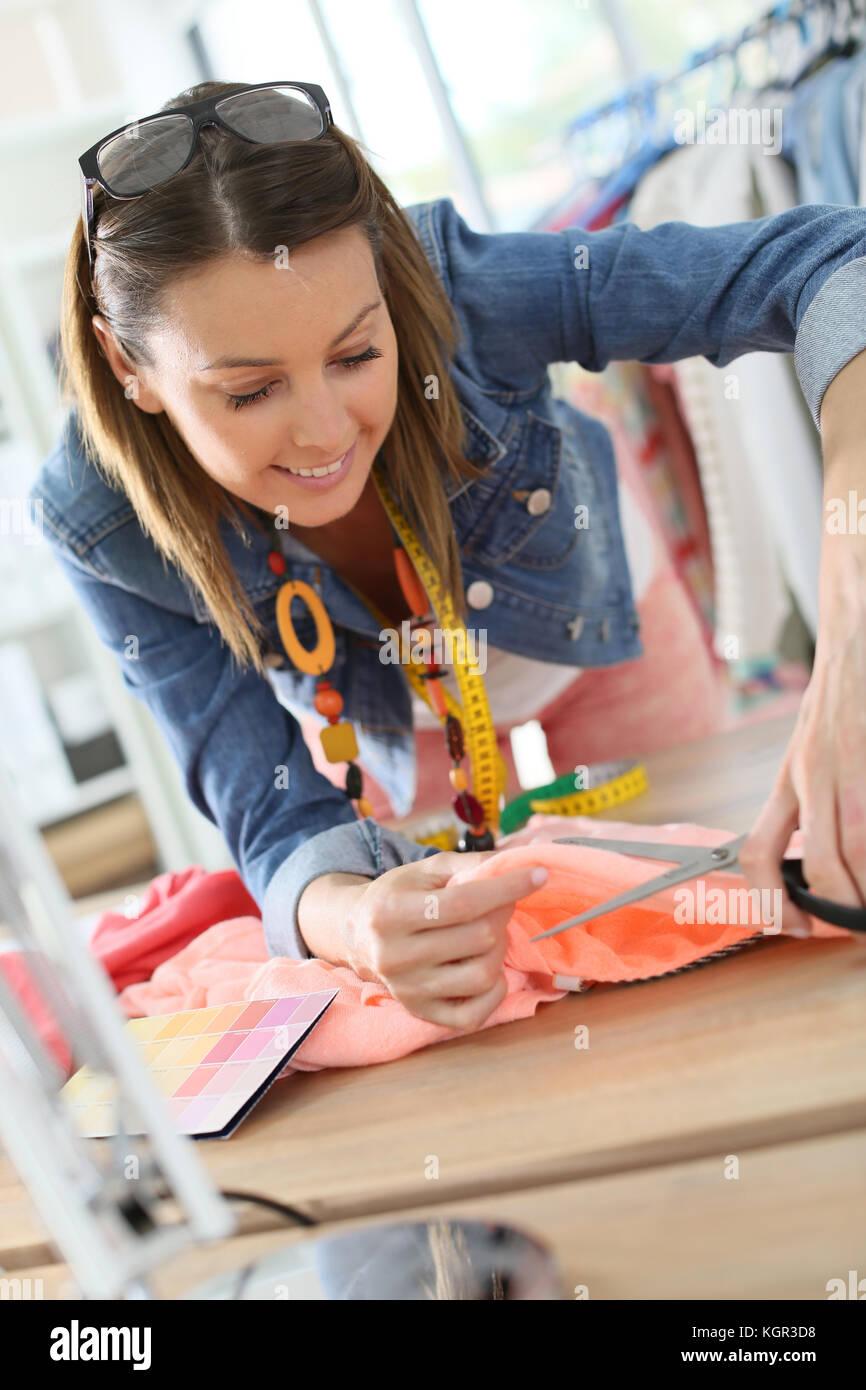 Designer di moda il taglio di tessuto sul tavolo sartoria Immagini Stock
