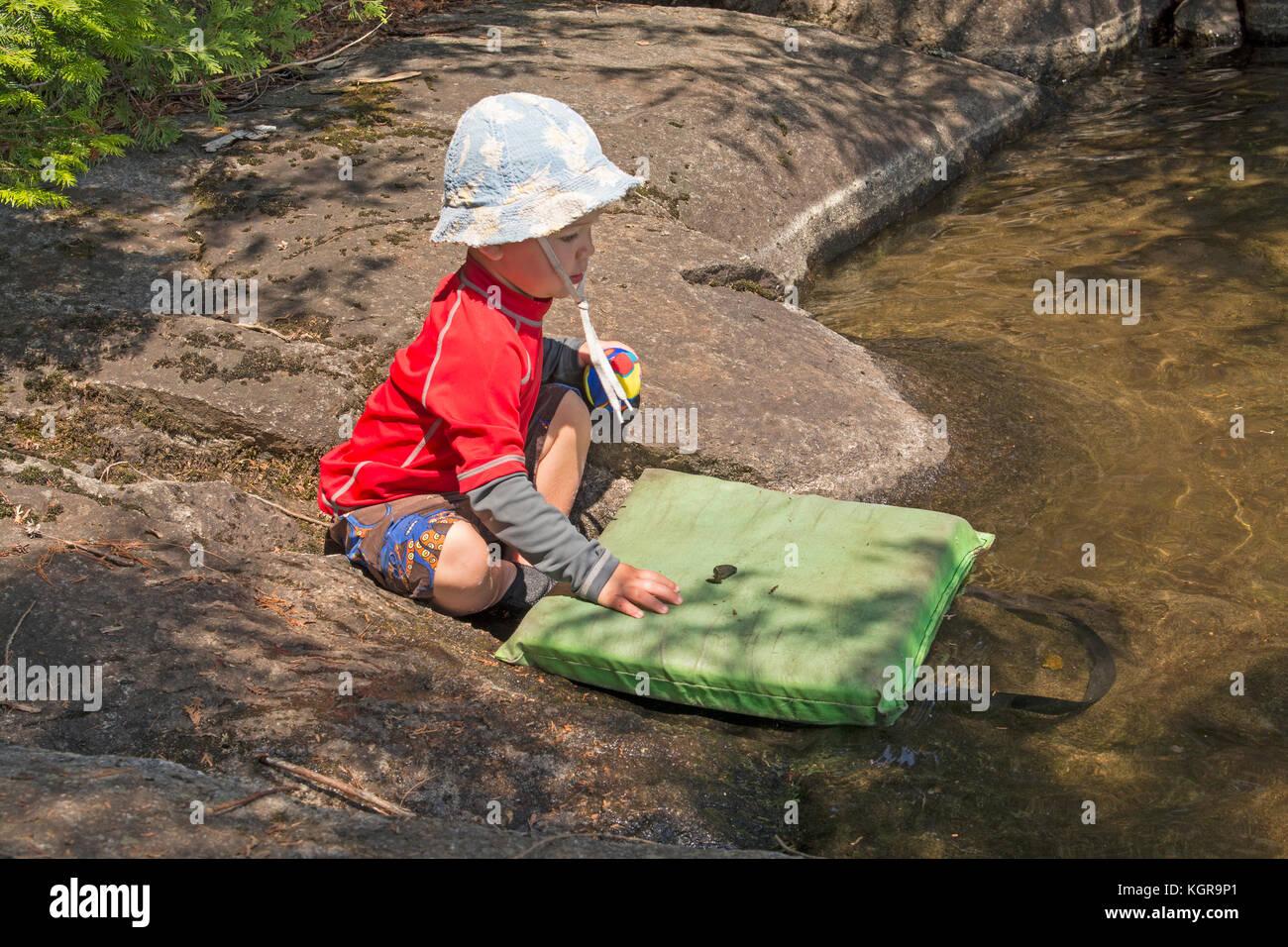 Little Boy giocando sulla riva del lago nella acque di confine del Minnesota Immagini Stock