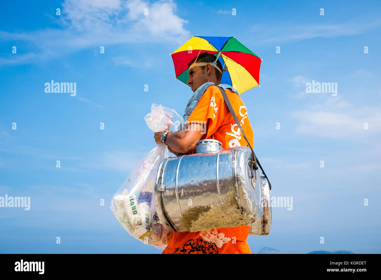 Rio de Janeiro - marzo 30, 2016: brasiliano spiaggia di vendita del fornitore del sud america tè mate passeggiate in uniforme con una pantina parasole hat lungo la spiaggia di Ipanema. Foto Stock