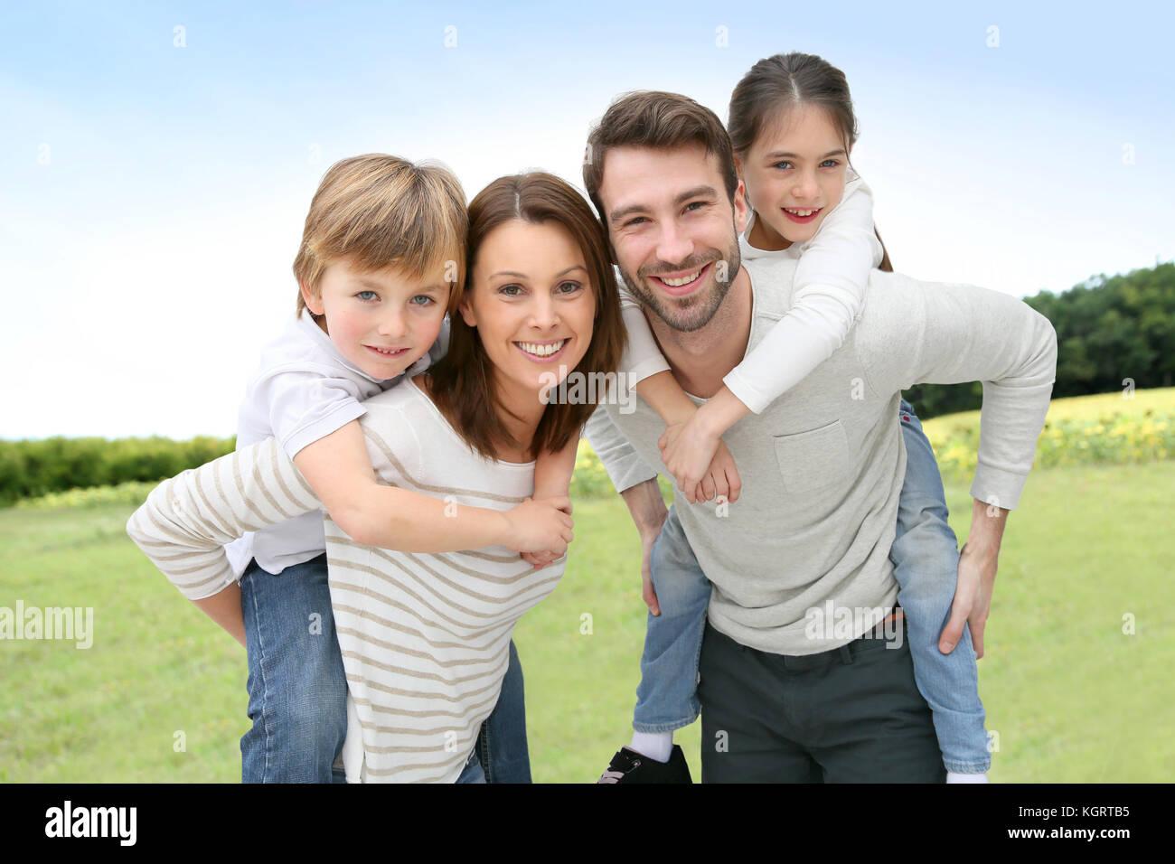 I giovani genitori dando piggyback ride per bambini Immagini Stock