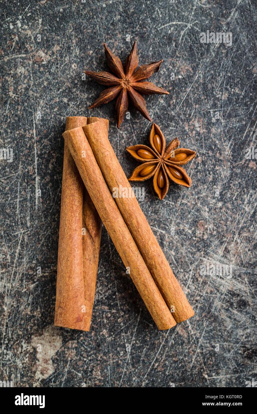 Bastoncini di cannella e anice stella sul vecchio tavolo da cucina. Immagini Stock