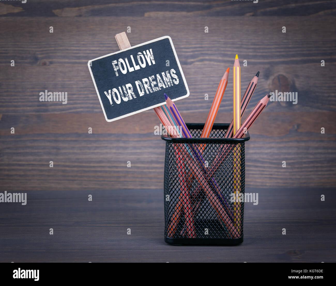 Seguire i tuoi sogni. Una piccola lavagna gesso e matita colorata su uno sfondo di legno Immagini Stock