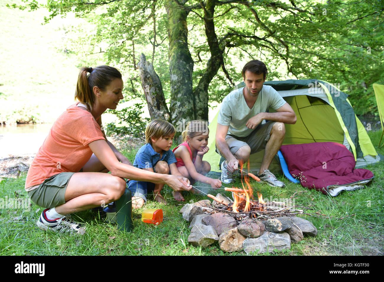 Famiglia campeggio e la cottura di salsicce in falò Immagini Stock