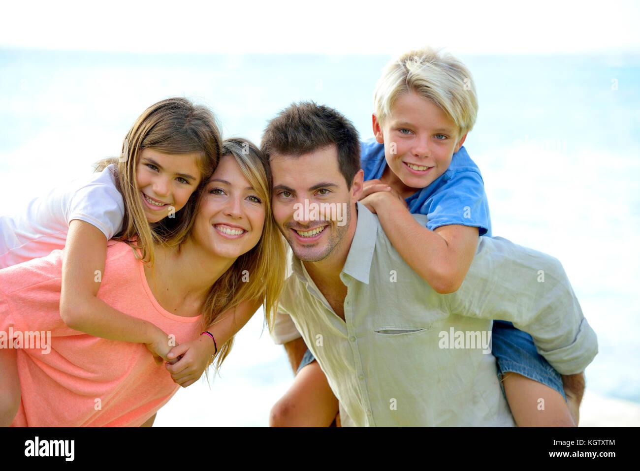 Allegro genitori tenendo i bambini sul loro retro Immagini Stock