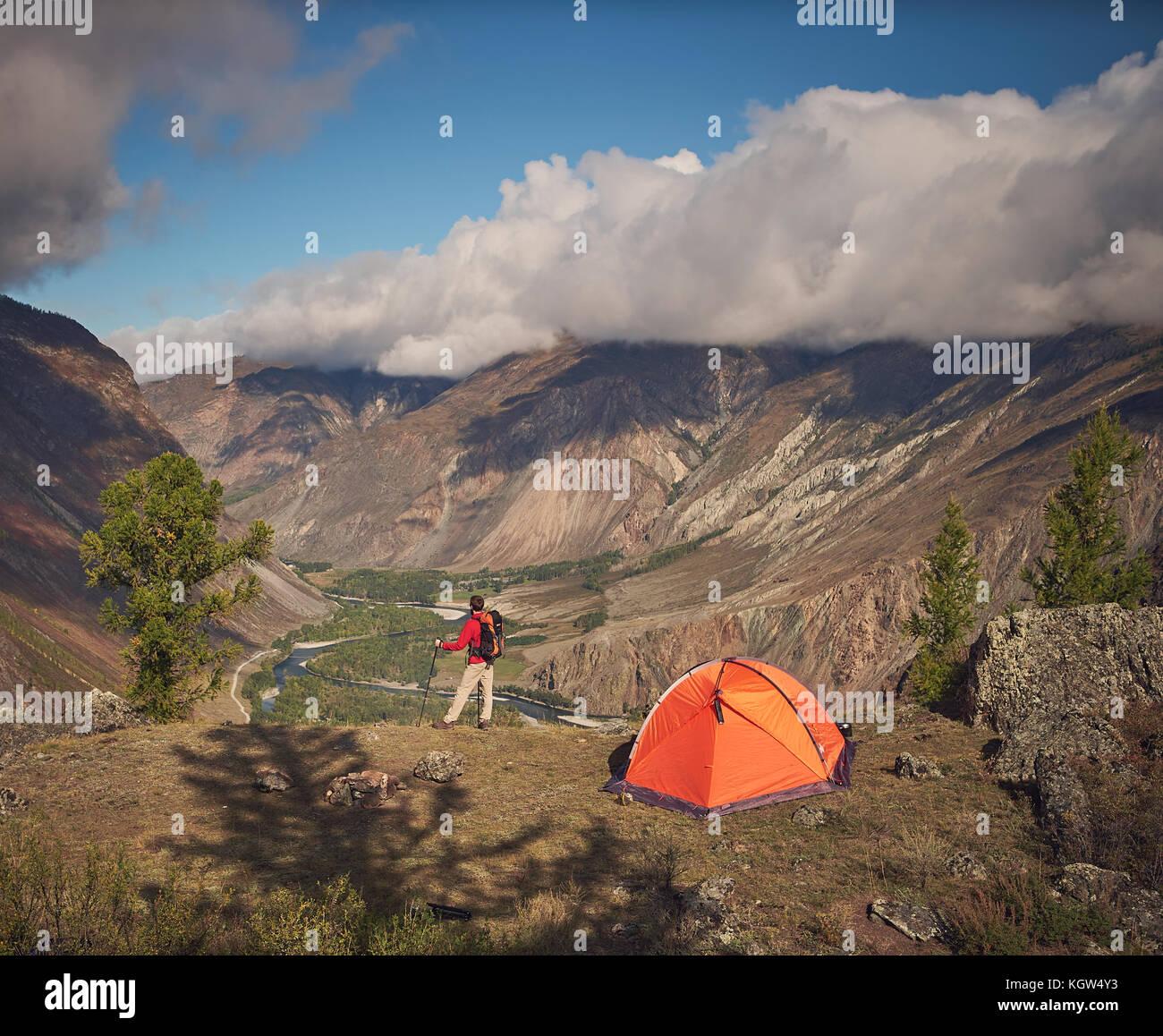 Persona che sorge nei pressi del campeggio e guardare la valle di montagna Immagini Stock