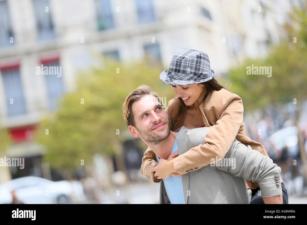 Giovane uomo dando piggyback ride per ragazza in città Immagini Stock