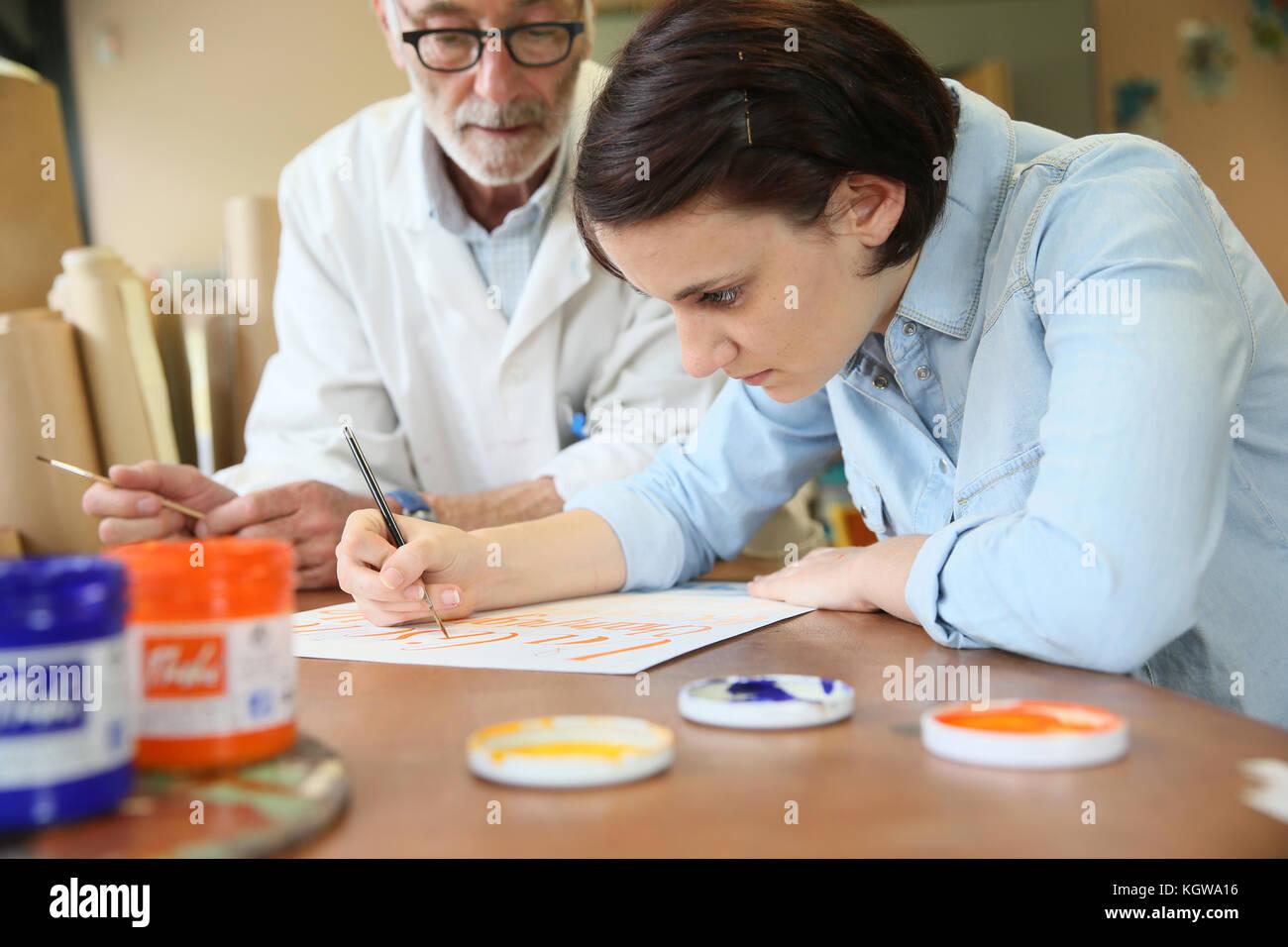 Giovane donna a scuola a studiare pittura decorativa Immagini Stock