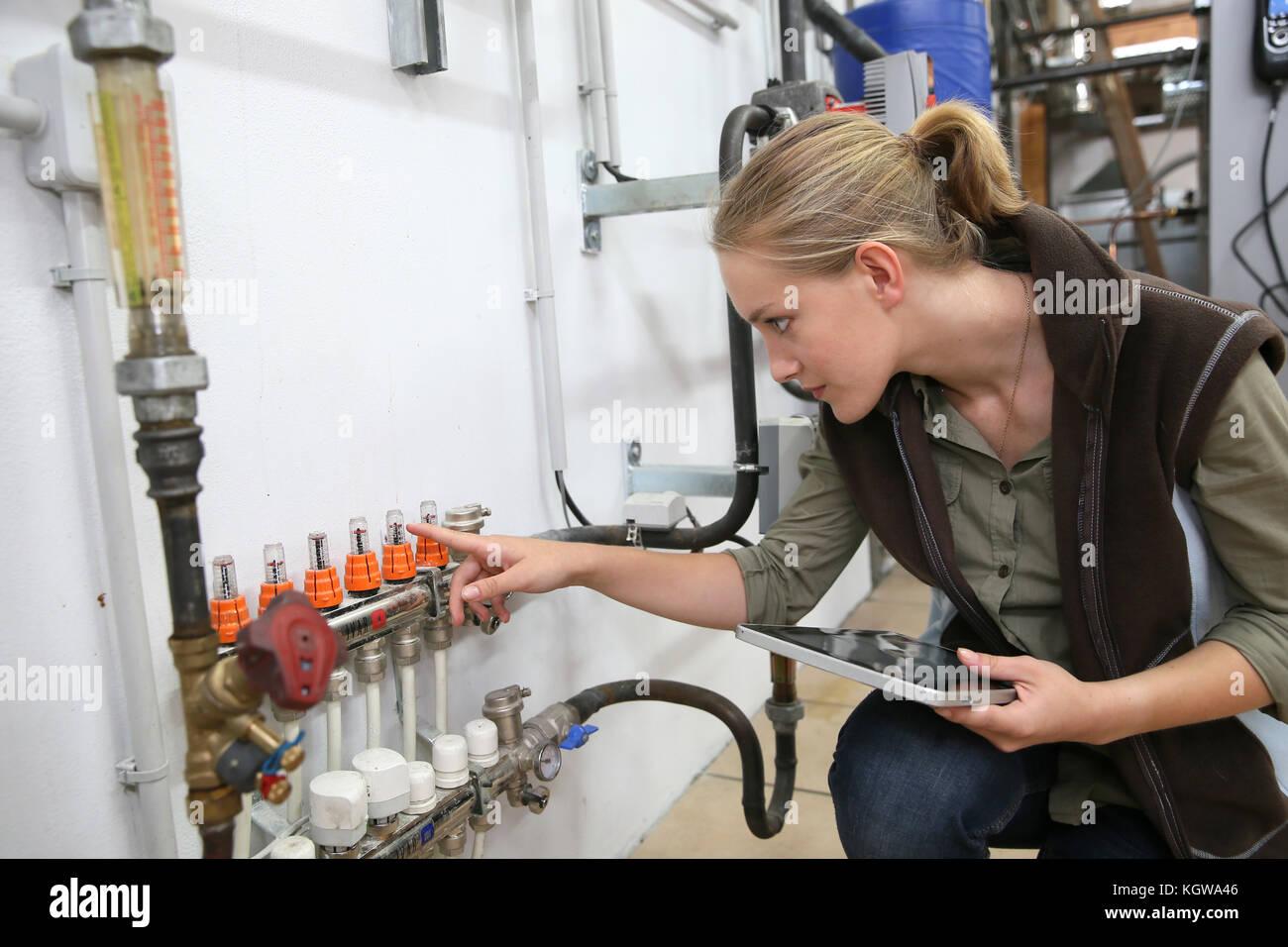 Giovane donna il controllo del livello di acqua in un macchinario Immagini Stock
