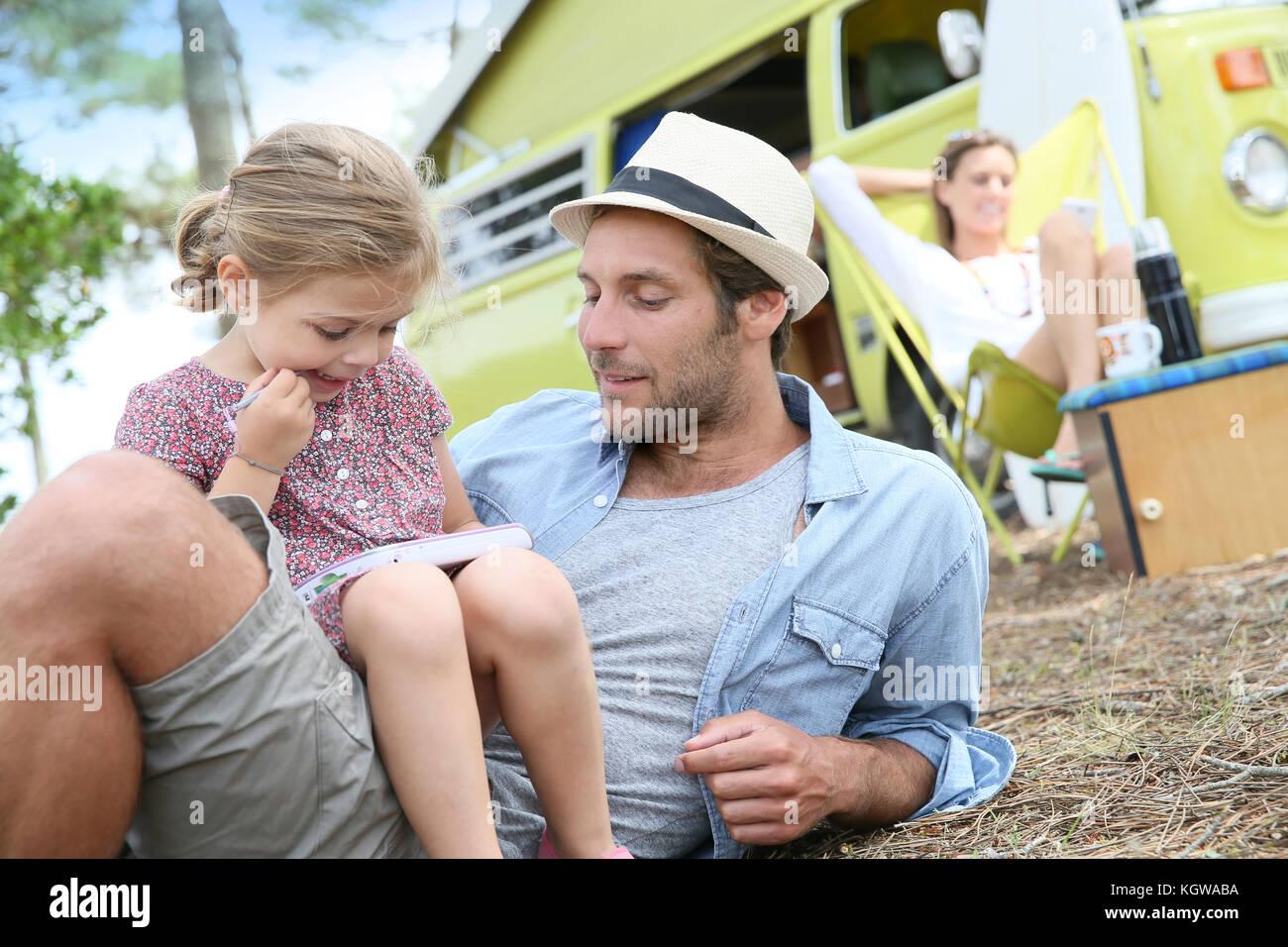 Il papà con bambina giocando insieme in campeggio Immagini Stock