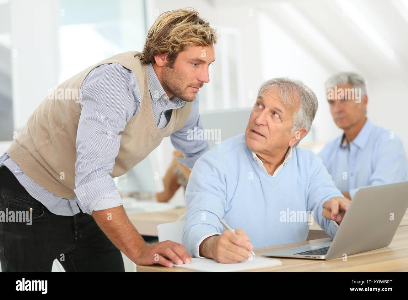 Senior uomo che frequentano la business class con trainer Immagini Stock
