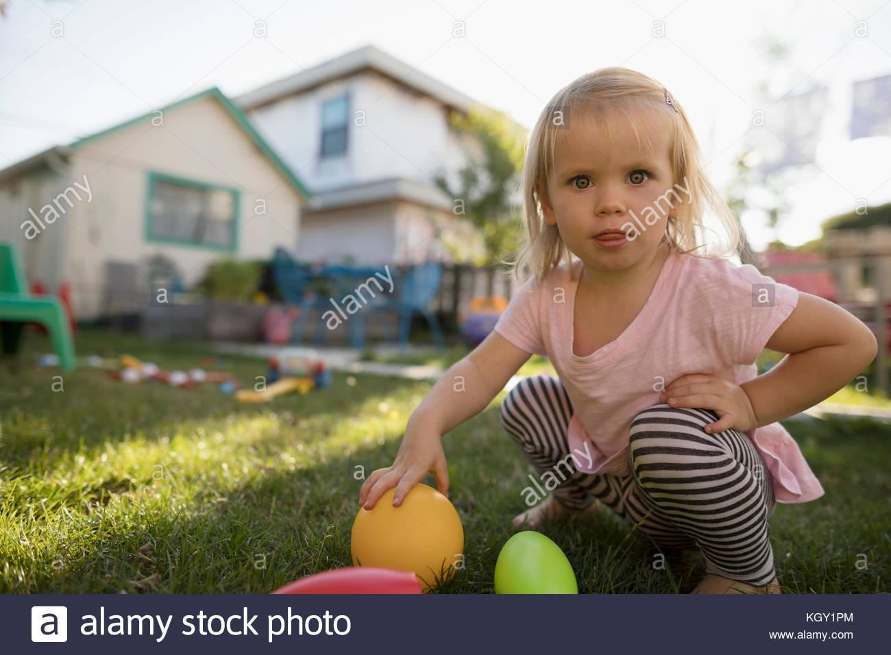 Ritratto curioso toddler bionda ragazza che gioca con i giocattoli in cortile Immagini Stock