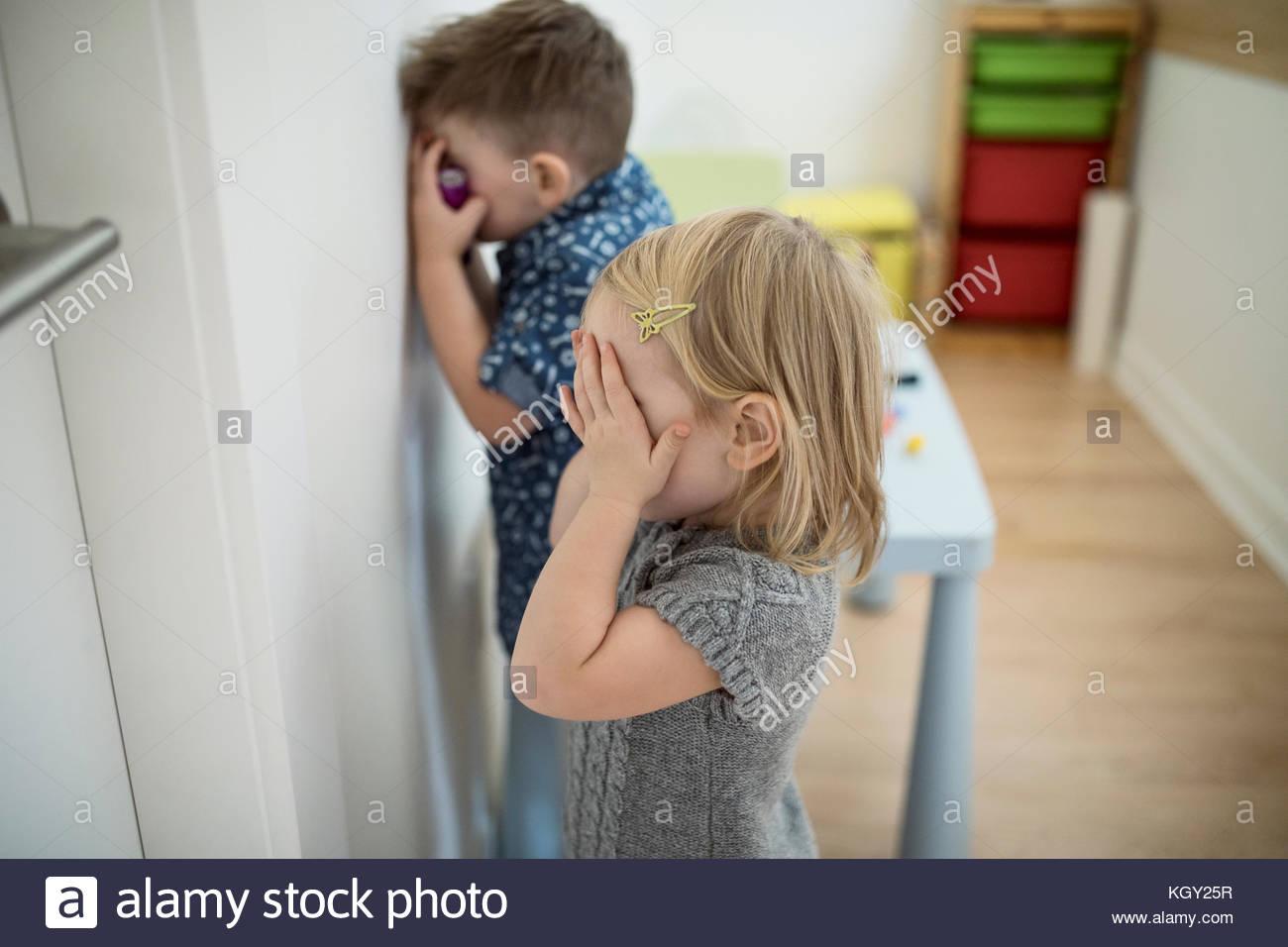 Il toddler fratello e sorella che copre gli occhi di giocare a nascondino gioco Immagini Stock
