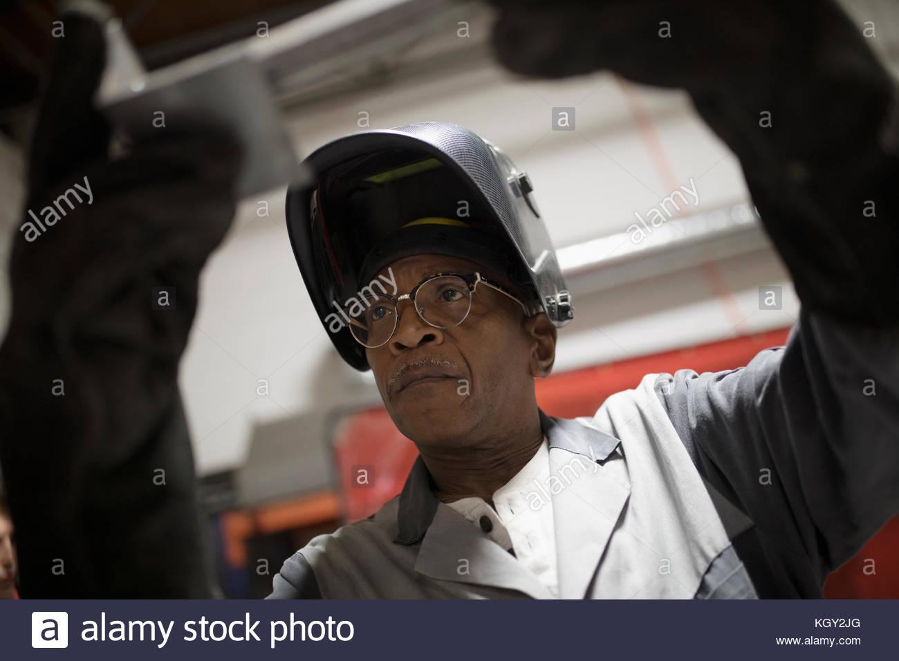Senior saldatore maschio esaminando pezzo metallico Immagini Stock