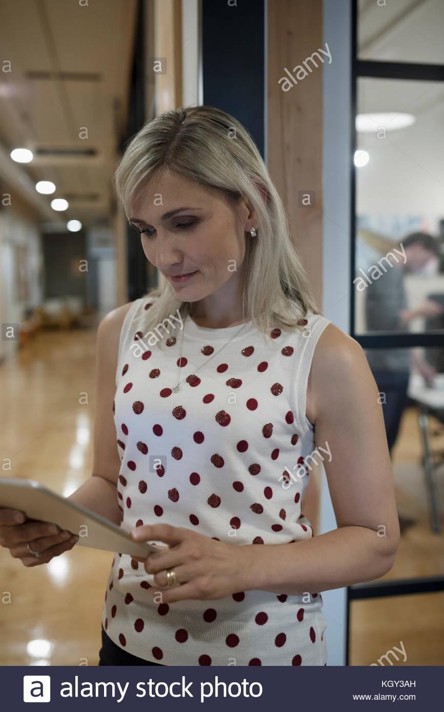 La bionda imprenditrice nella polka-dot shirt utilizzando digitale compressa nel corridoio di office Immagini Stock