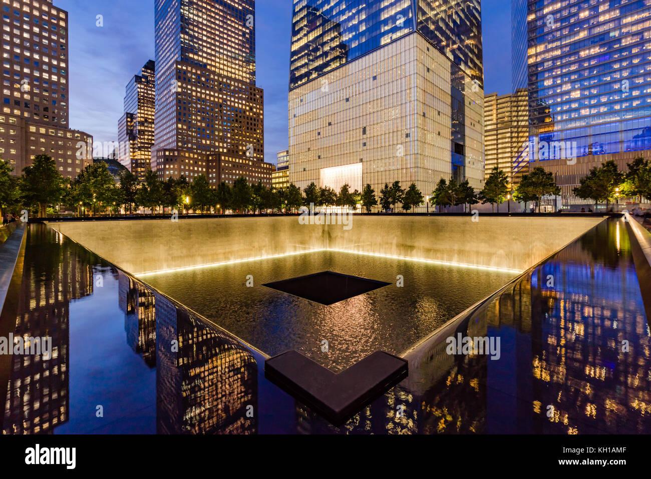 Il Nord Pool riflettente illuminato al crepuscolo con vista di One World Trade Center. La parte inferiore di Manhattan, Immagini Stock