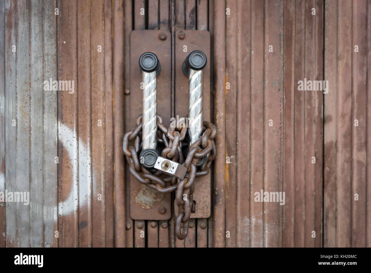 Lucchetto a catena e bloccato in modo sicuro sulla porta arrugginito. Immagini Stock