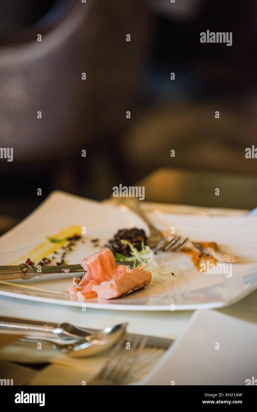 Una metà mangiato il salmone confit di quinoa e piatto di insalata Immagini Stock