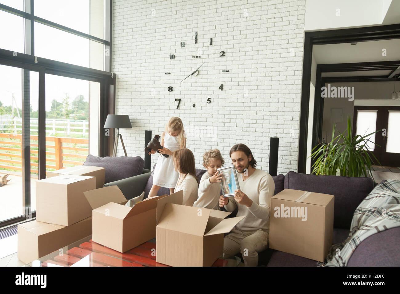 Giovane famiglia felice con bambini disimballaggio scatole insieme ...