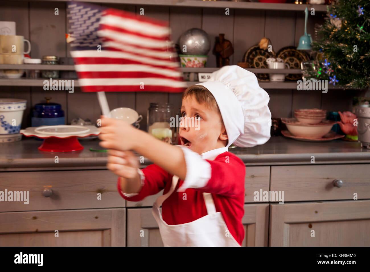Giovane uomo sventolare la bandiera americana in cucina per natale ...