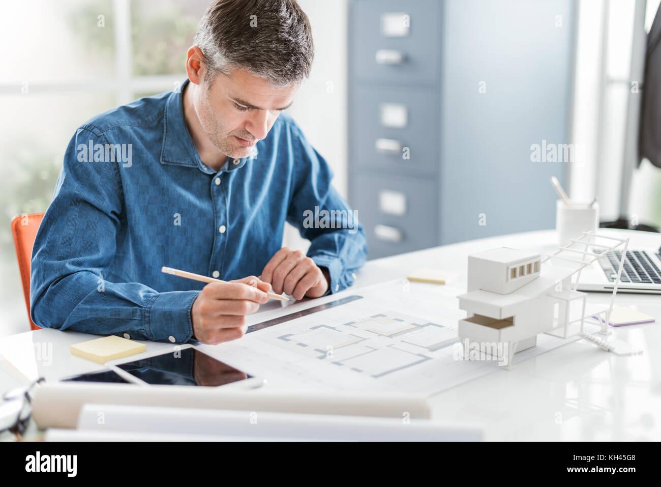 Disegno Uomo Alla Scrivania : Architetto professionista lavora alla scrivania in ufficio egli è