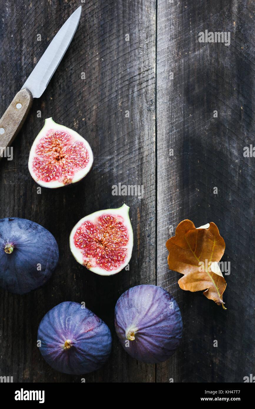 Viola fresca di fichi e coltello da tavola sul vecchio sfondo di legno con copia spazio per il testo. Vista superiore Immagini Stock