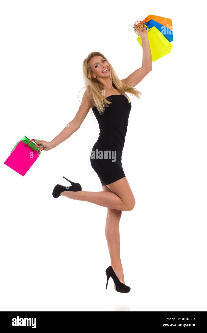 Felice donna bionda in nero mini abito e tacchi alti e