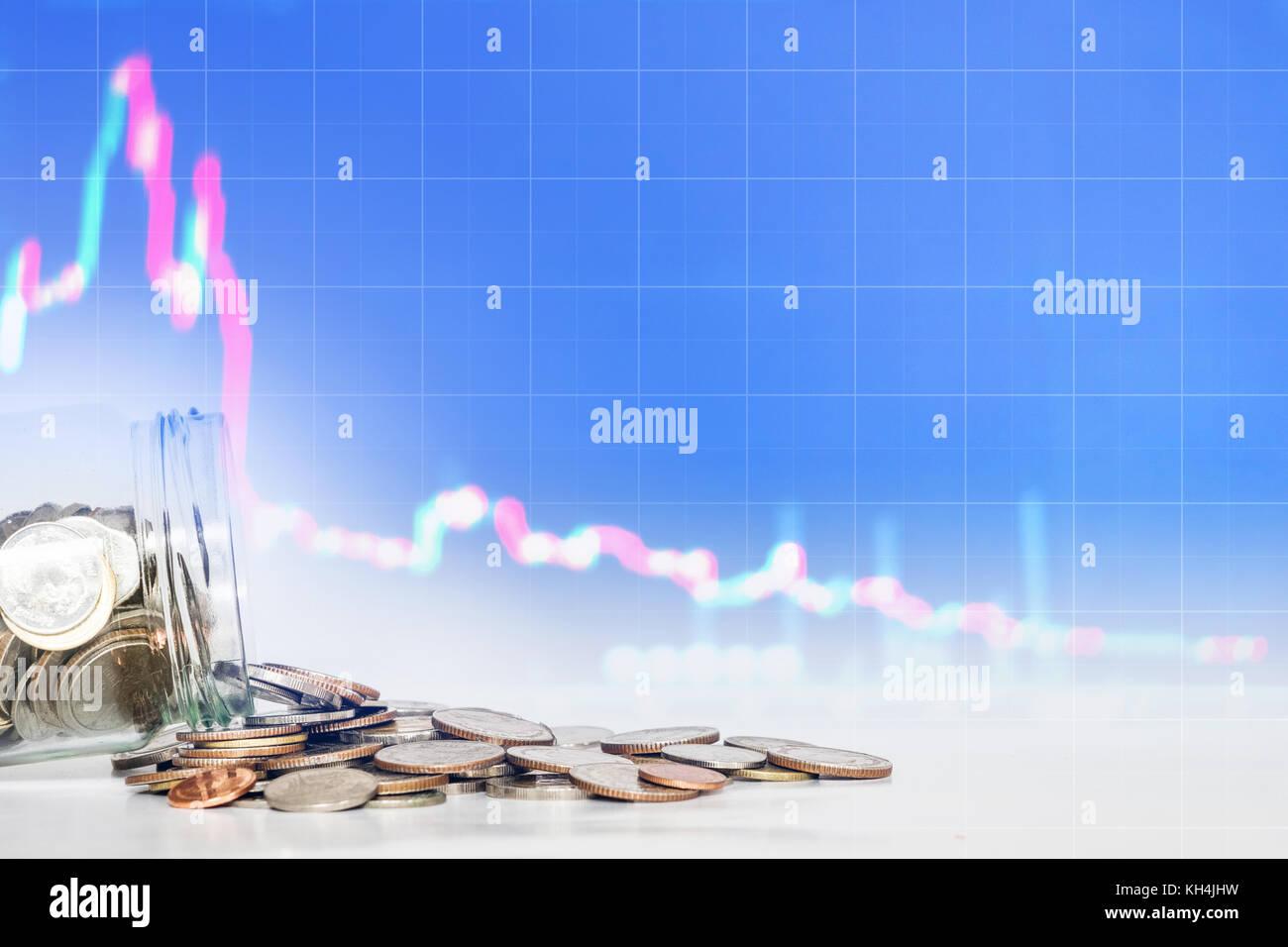 Monete spillato dal vaso di vetro con la caduta verso il basso sullo sfondo del grafico. perde il denaro, il fallimento Immagini Stock
