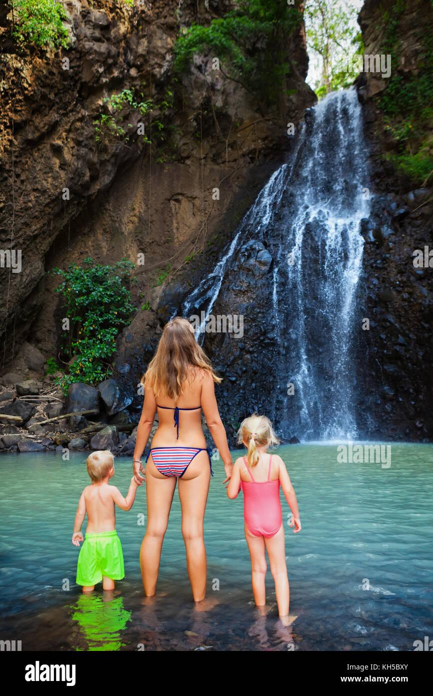 Madre, bambini nuotare nella piscina di acqua sotto la cascata nel canyon nella giungla. viaggi avventura, escursionismo Immagini Stock