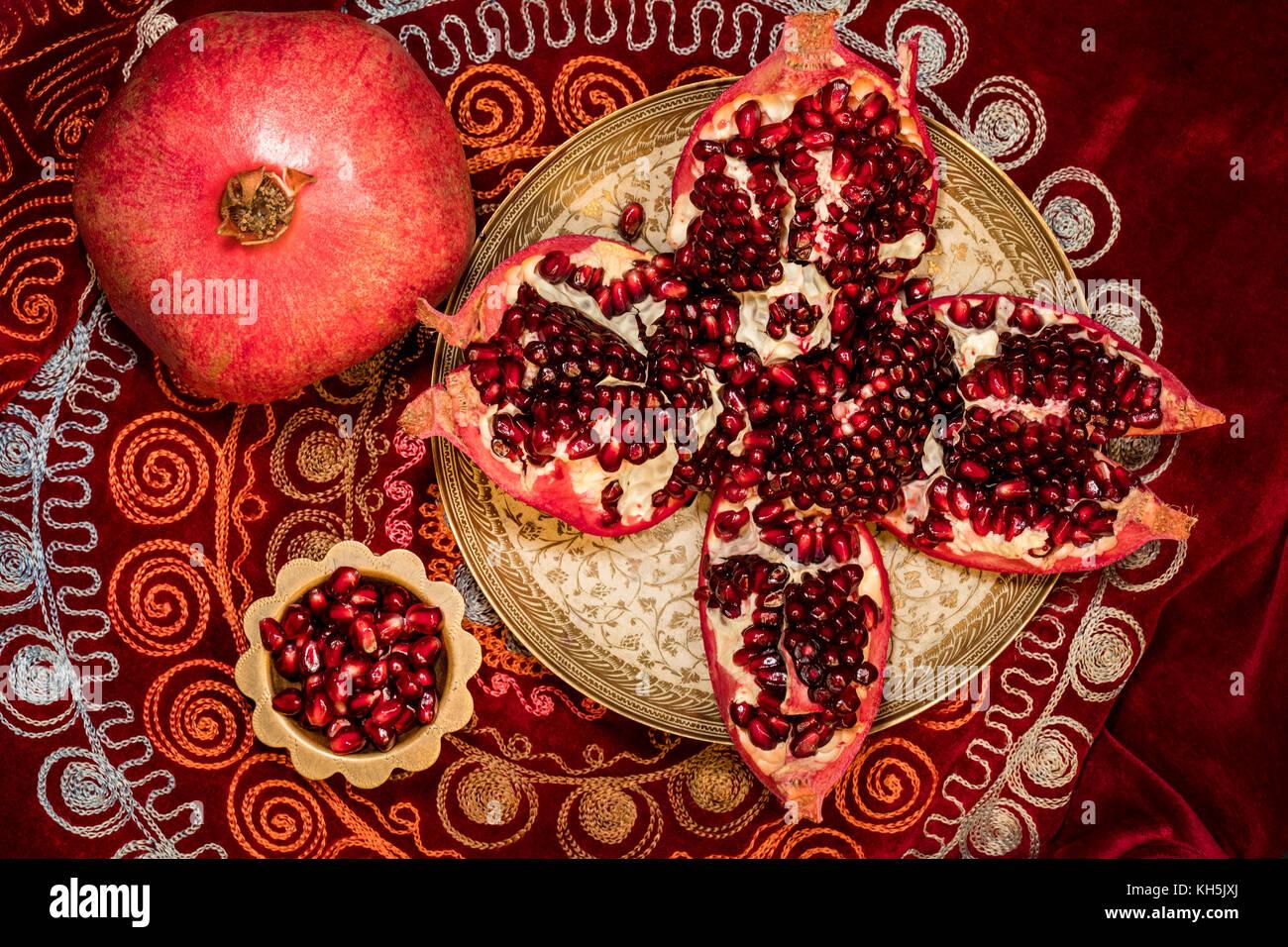 Vista superiore dei pomodori pelati melograno e grani di ruby in una ciotola sulla tovaglia orientali Immagini Stock