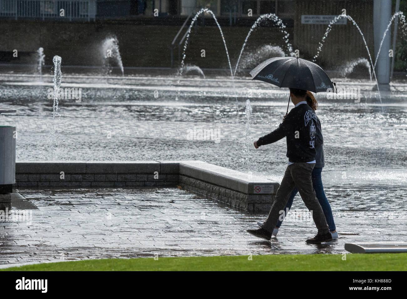 Giovane a piedi sotto la pioggia, rifugiandosi sotto ombrellone, passando la piscina a specchio e fontane - centro Foto Stock