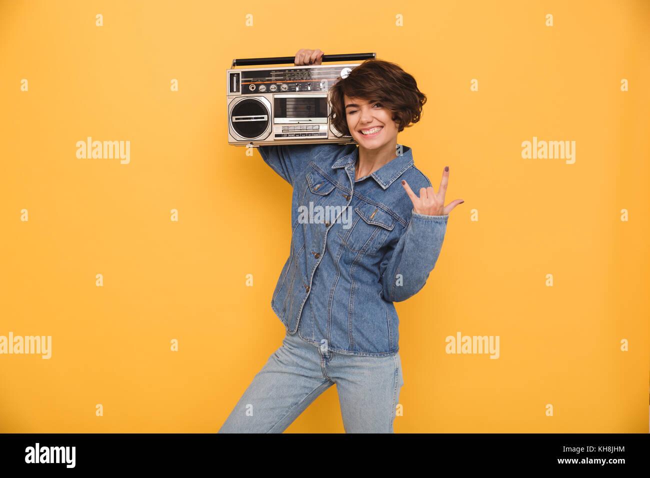 Ritratto di un allegro sorridente ragazza vestita in camicia denim holding  record giocatore sulla sua spalla 56fc14a835fa