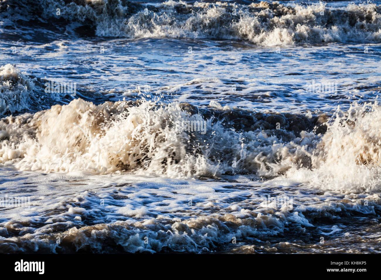 Onde che si infrangono contro la riva. Foto Stock