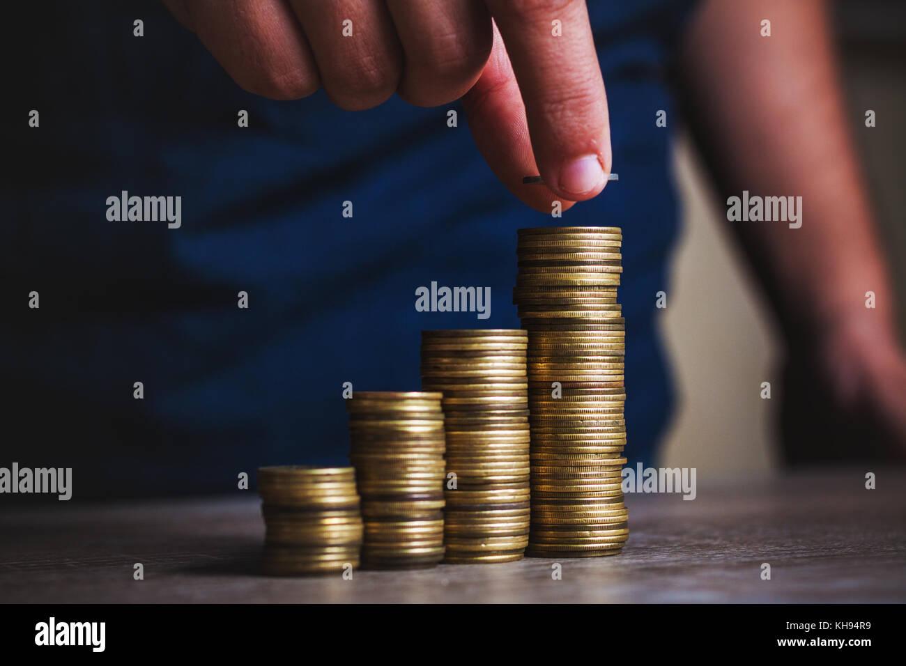 Mano d'uomo messo il denaro delle monete per pila di monete. denaro, finanziari, crescita aziendale concept Immagini Stock