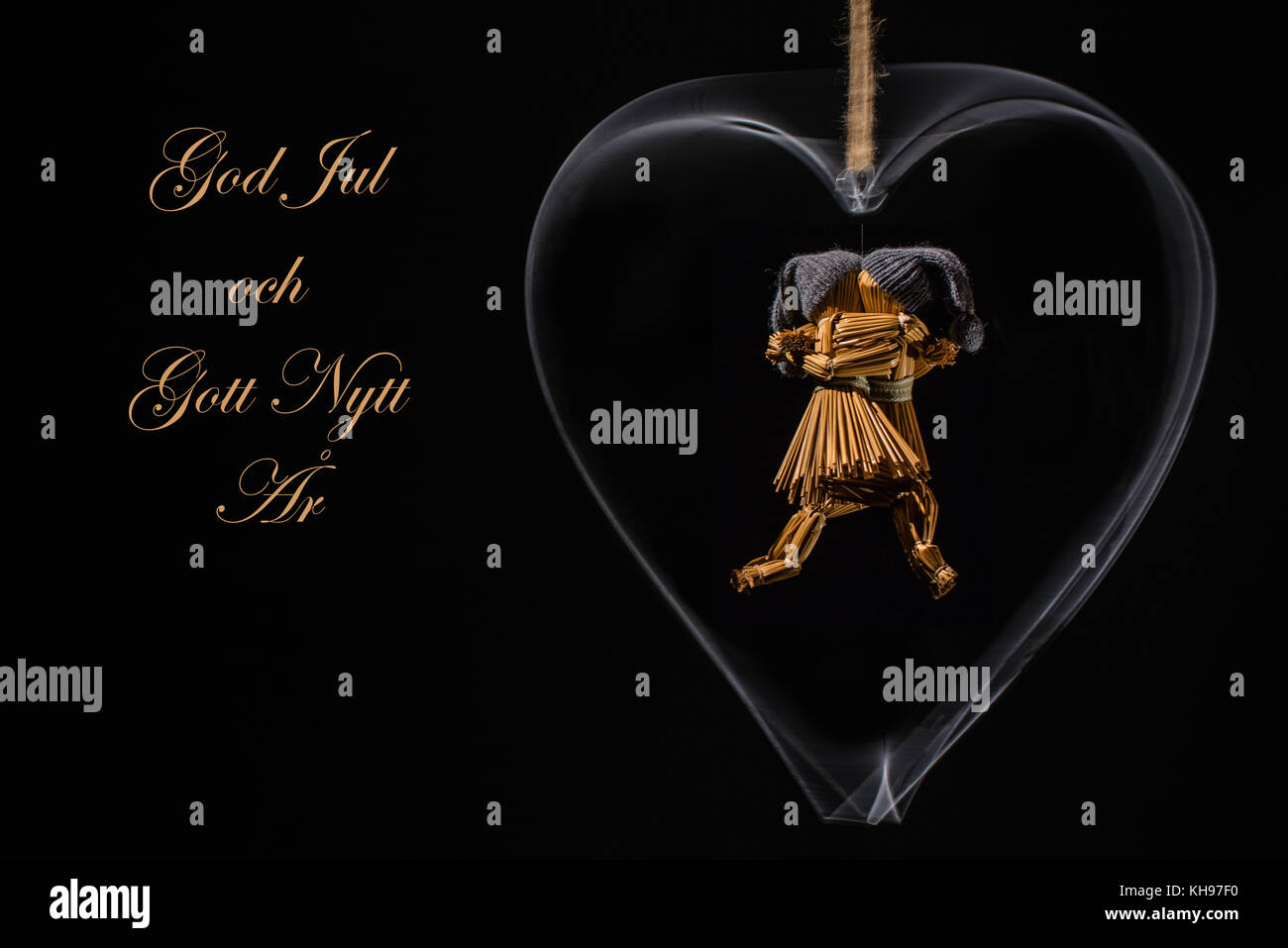 Auguri di Natale in svedese con il ballo delle bambole di paglia in una rotazione cuore di metallo e con il testo: Immagini Stock