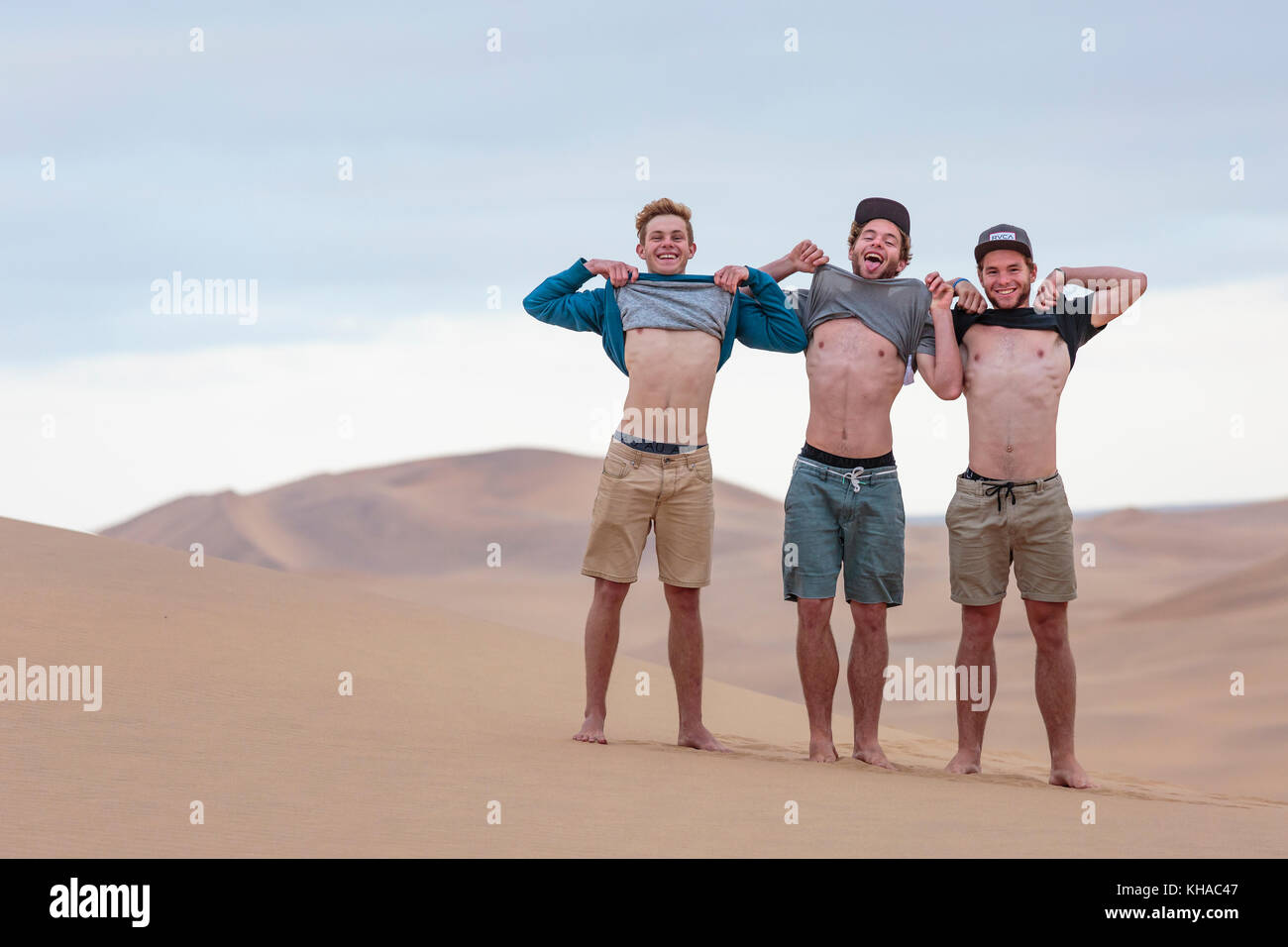 Tre giovani uomini mostrano la loro forza muscolare del corpo superiore, Namib Desert, Namibia Immagini Stock