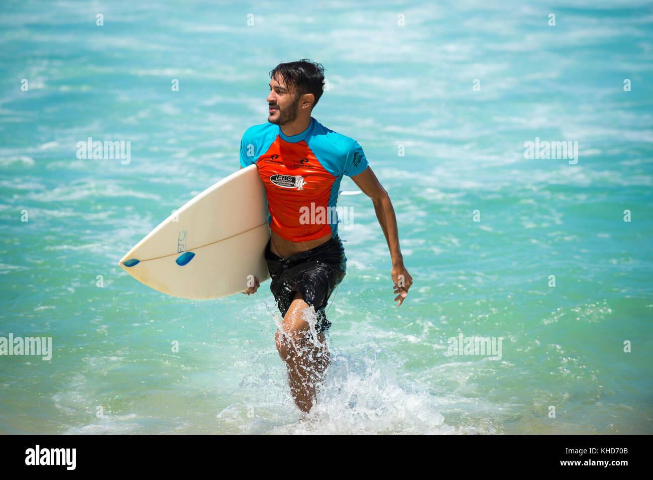 Rio de Janeiro - febbraio 9, 2017: giovane brasiliano surfer cammina con la sua tavola da surf attraverso le onde Immagini Stock