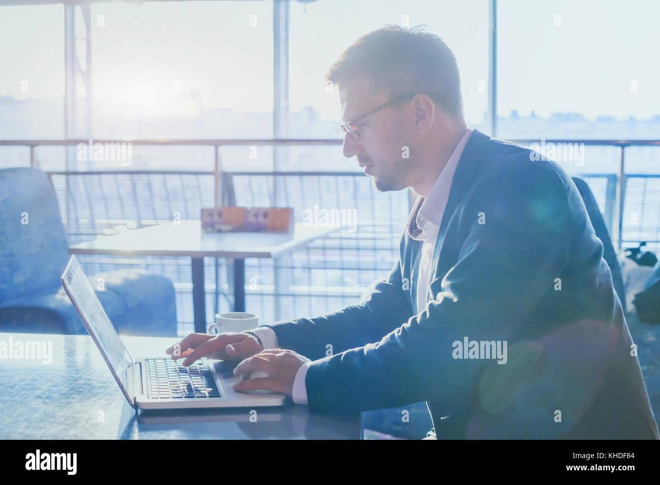 Imprenditore lavora su computer in ambienti moderni di aeroporto cafe, uomo utilizzando internet sul computer portatile, Immagini Stock