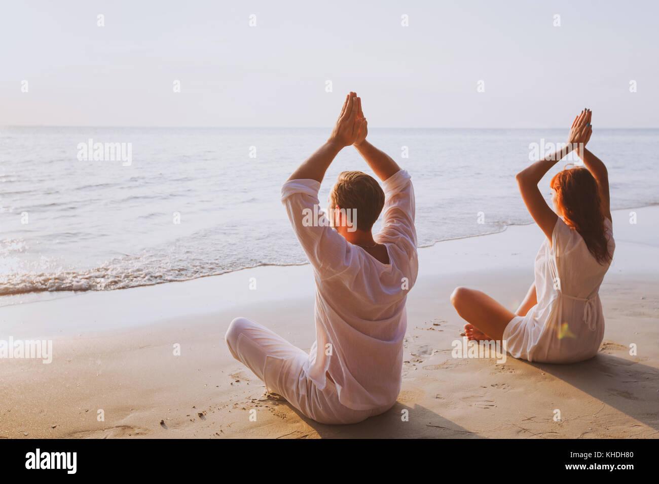 La meditazione di gruppo, yoga sulla spiaggia al tramonto Immagini Stock
