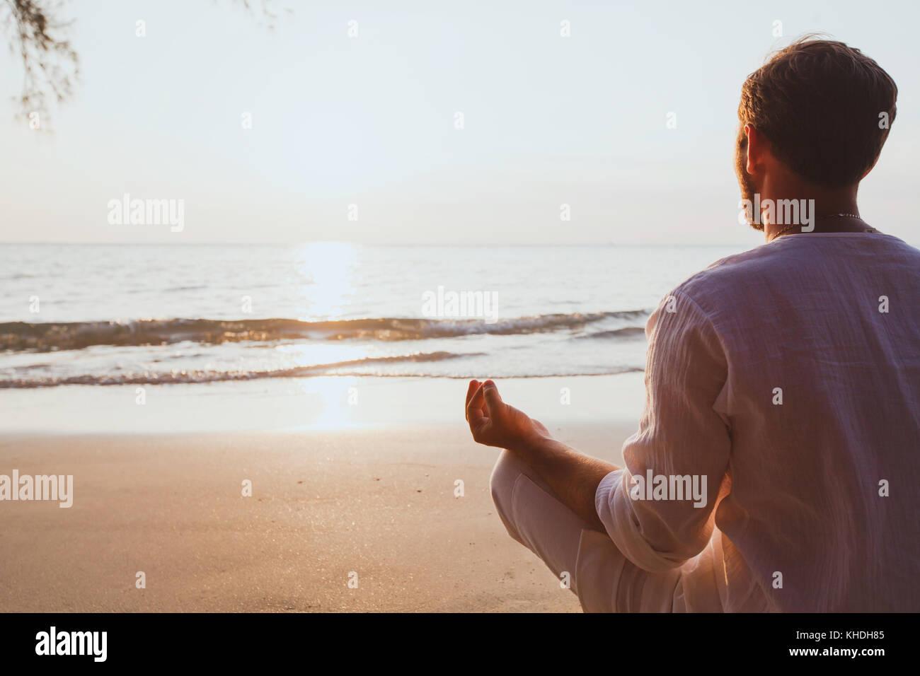 La meditazione, l'uomo la pratica dello yoga a Sunset beach, con uno sfondo con spazio di copia Immagini Stock