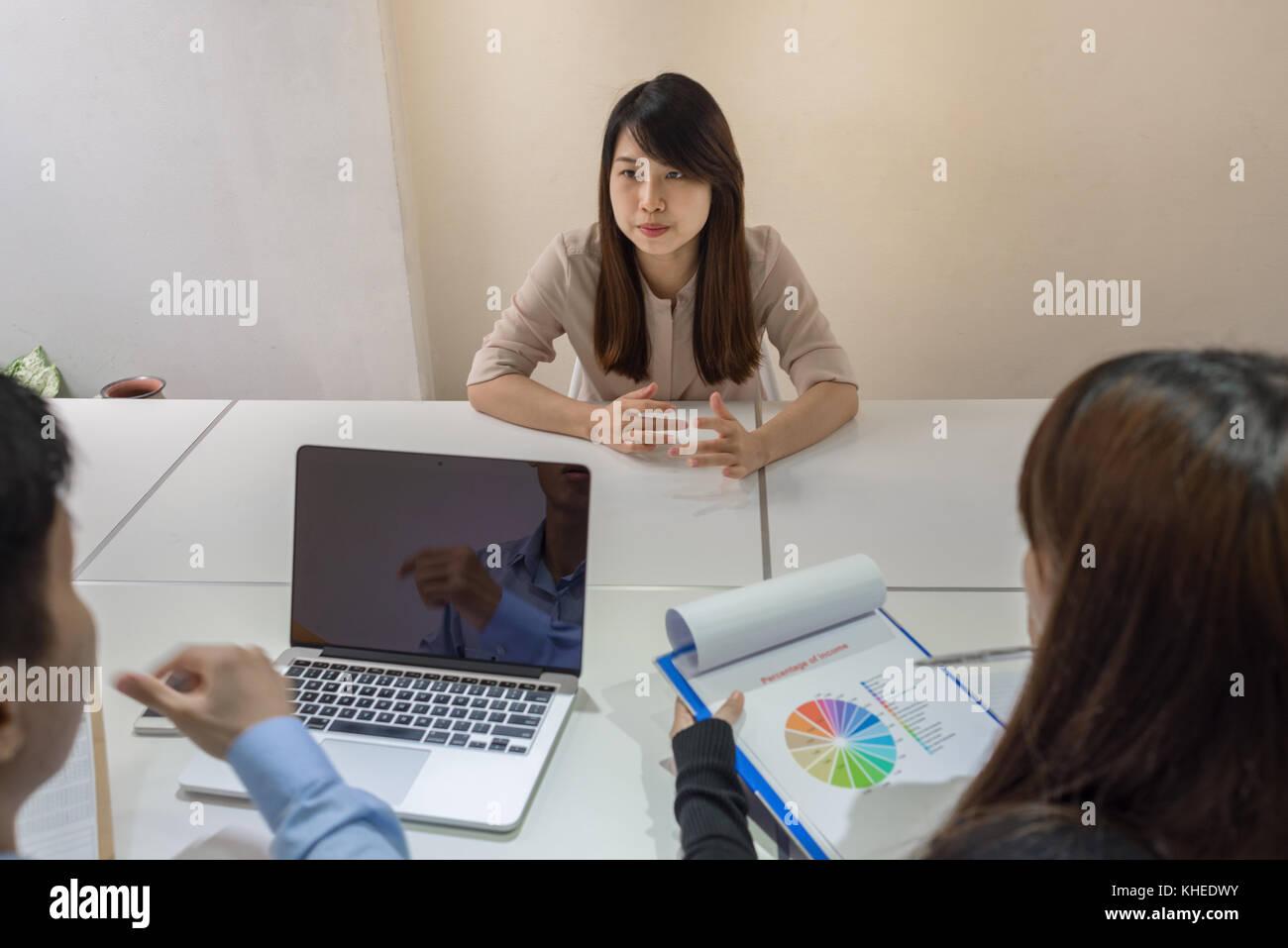 Dipendente asiatici spiegare circa il cattivo risultato Immagini Stock