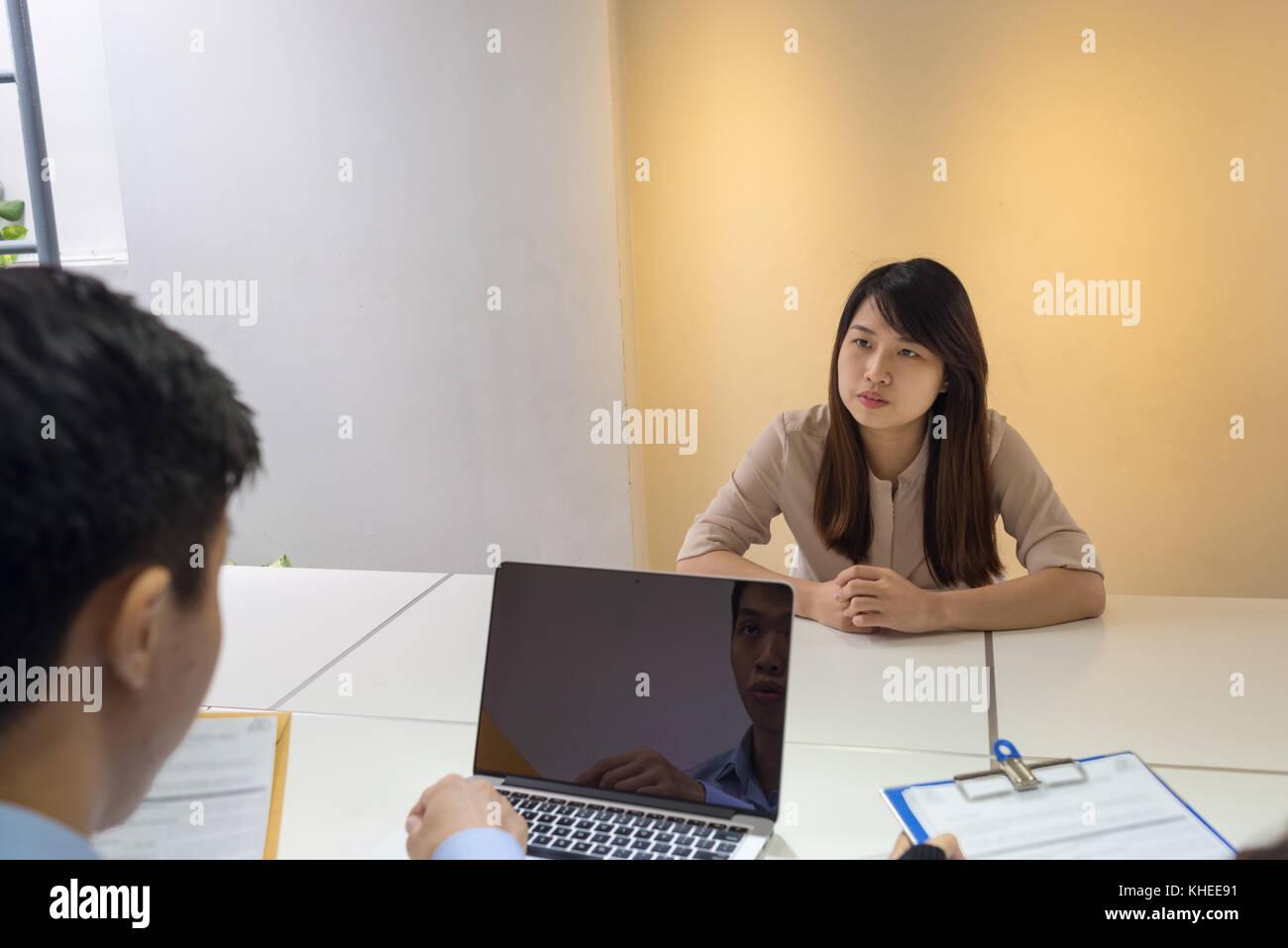 Giovani asiatici il candidato risponde alle domande poste da intervistatori Immagini Stock