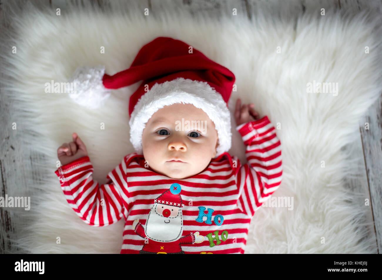 Ritratto di natale di carino piccolo neonato bambino vestito in abiti di  natale e indossando santa hat 82fa4e9656aa