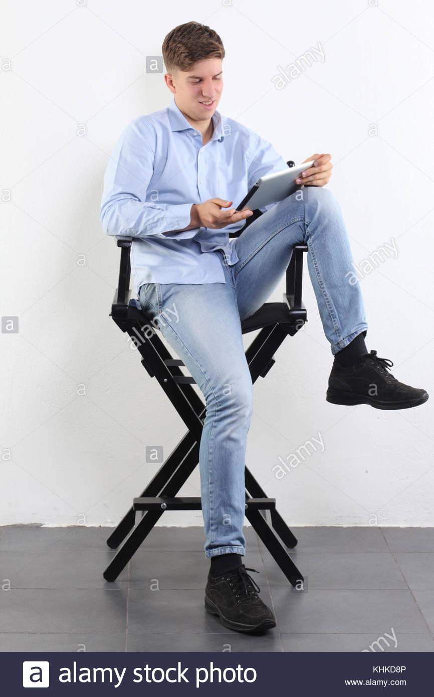 Boy utilizzando un tablet seduto su un sgabello nero Immagini Stock
