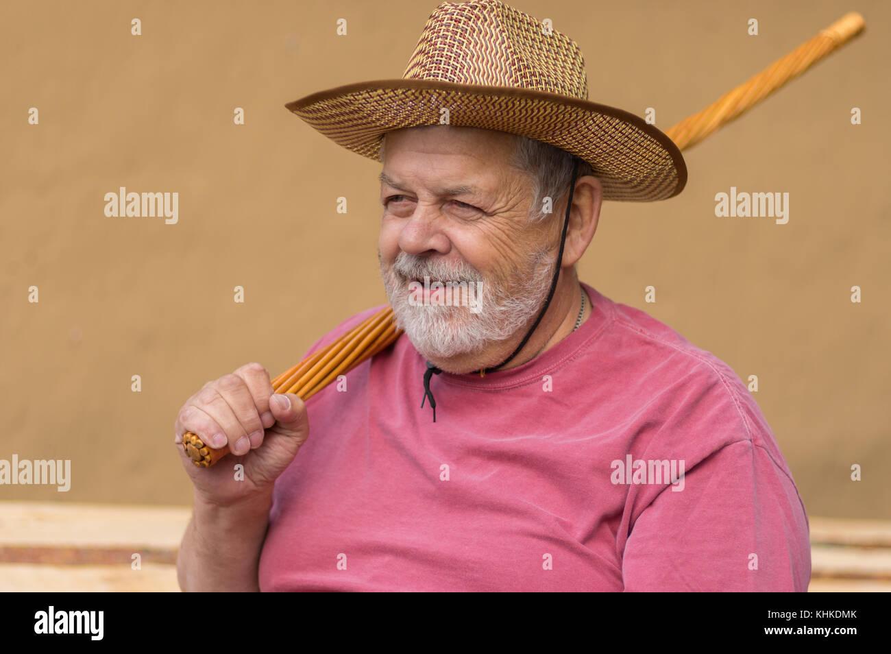 Bel ritratto del barbuto senior uomo nel cappello di paglia seduto contro  la parete di argilla e azienda vimini bastone su una spalla ce27f0eb2a59
