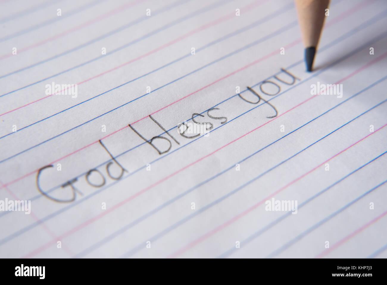 """Scrittura a mano utilizzando una matita su un foglio di carta.scrivere """" Dio vi benedica"""" Foto Stock"""
